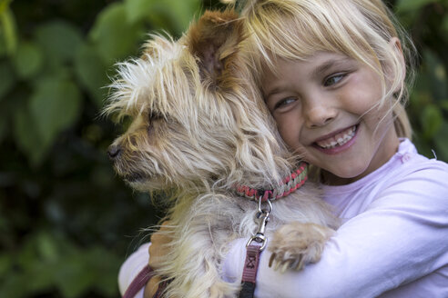 Portrait of happy little girl cuddling her dog - JFEF00866