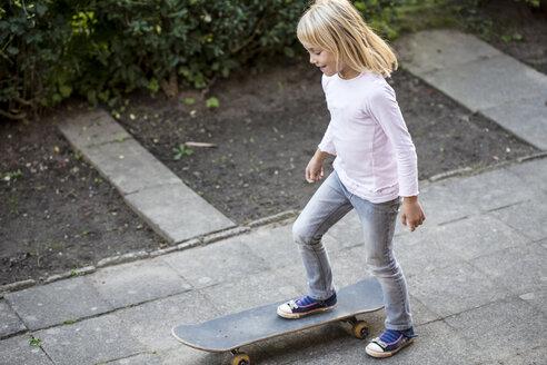 Smiling little girl with skateboard - JFEF00869