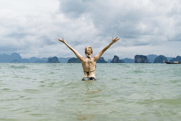 Thailand, Koh Yao Noi, back view of happy woman standing in the sea - CHPF00471