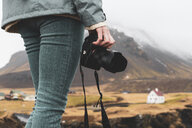 Iceland, woman with camera, partial view - KKAF00997