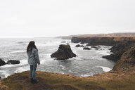 Iceland, back view of woman standing at coast - KKAF01003