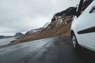 Iceland, white car on wet coastal road - KKAF01018
