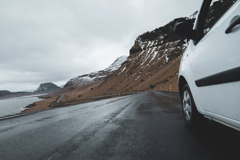 Iceland, white car on wet coastal road - KKAF01018