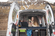 Portrait of young woman lying in van using smartphone and laptop - KKAF01021