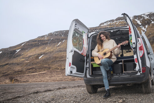 Iceland, woman in front of van playing guitar - KKAF01024