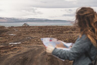 Iceland, woman with map in  landscape with single house - KKAF01027