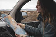 Iceland, young woman in car looking at map - KKAF01030