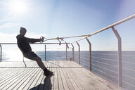 Man practicing suspension training on a promenade around the sea - SKCF00453