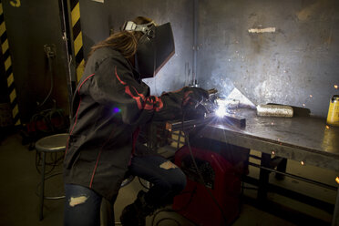 Female metalsmith welding metal at workbench - ISF04608