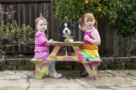 Two young sisters sitting on garden bench with pet dog - ISF04638