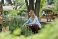 Young woman tending to plants in urban garden - ISF04653