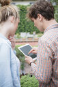 Couple in garden using digital tablet - ISF04662