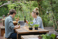Couple with beer in garden using laptop - ISF04677