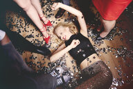 Woman fooling around on floor at party, friends standing around her, glitter on floor, elevated view - ISF04759