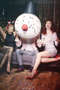 Friends sitting together at party, man holding snowman head in front of face, women laughing - ISF04768