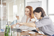 Businesswomen with coffee having discussion in meeting - ISF04783