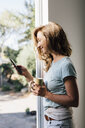 Happy young woman at patio door looking at smartphone - ISF04825