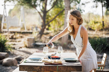 Young woman, outdoors, preparing dinner table, pouring wine - ISF04828