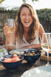 Portrait of young woman, outdoors, sitting at table, holding wine glass - ISF04831