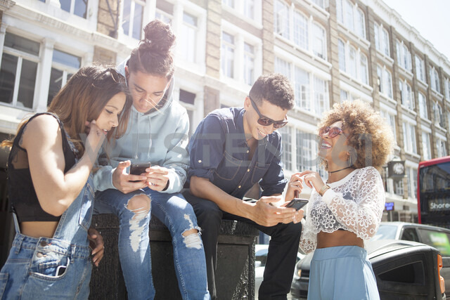 Four young friends outdoors, looking at smartphone - ISF04867