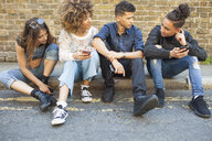 Four friends sitting in street, looking at smartphones - ISF04873