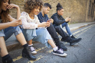 Four friends sitting in street, looking at smartphones - ISF04879
