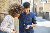 Young couple in street, looking at smartphone - ISF04936