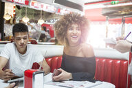 Young couple sitting in diner giving order to waitress - ISF04939