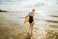 Young woman carrying surfboard in sea, Folkestone, UK - ISF05053