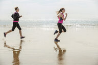 Mother and daughter running on beach, Folkestone, UK - ISF05059