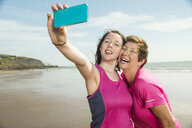 Mother and daughter taking selfie on beach, Folkestone, UK - ISF05068