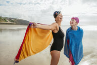 Mother and daughter standing on beach with shawls, Folkestone, UK - ISF05113