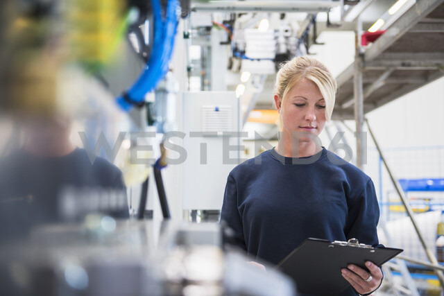 Factory worker looking at paperwork on clipboard - ISF05344