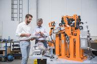 Two engineers looking at digital tablet in engineering factory - ISF05377
