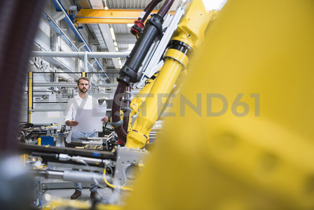 Young male engineer looking at blue print in engineering factory - ISF05410 - Daniel Ingold/Westend61