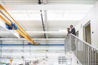 Supervisor and manager looking out from top of distribution warehouse stairway - ISF05449