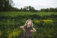 Portrait of girl with wavy blond hair laughing in field - ISF05467