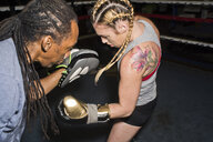 Female boxer punching trainer's boxing mitt in boxing ring - ISF05482