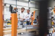 Two engineers using digital tablet talking in engineering factory - ISF05557