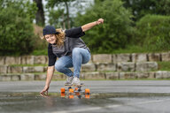 Young woman balancing on skateboard - STSF01580