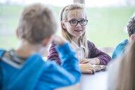 Portrait of smiling schoolgirl with classmates in class - WESTF24081