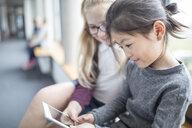 Schoolgirls sharing a tablet on school corridor - WESTF24093