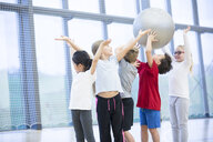 Pupils handing over gym ball in gym class - WESTF24096