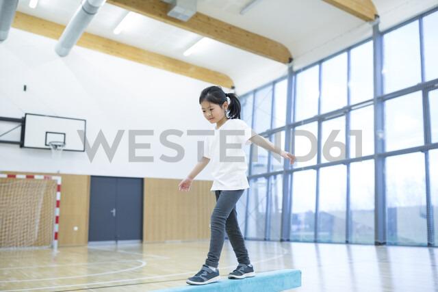 Schoolgirl balancing on balance beam in gym class - WESTF24105