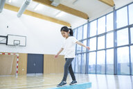 Schoolgirl balancing on balance beam in gym class - WESTF24105