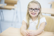 Portrait of smiling schoolgirl in class - WESTF24111