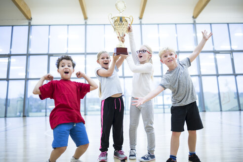 Happy pupils holding trophy in gym - WESTF24114