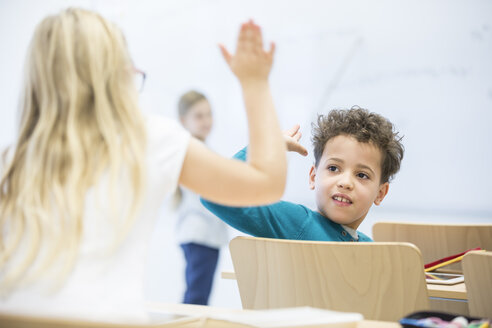 Pupils high fiving in class - WESTF24120