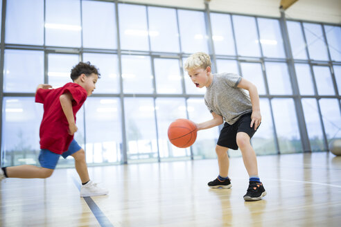 Two schoolboys playing basketball in gym class - WESTF24129