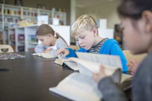 Pupils reading books on table in school break room - WESTF24141
